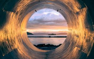 View inside of a tube to ocean and sunset